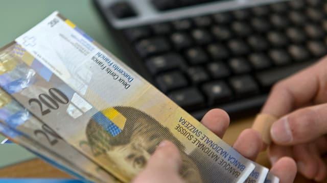 Schweizer Banknoten liegen in einer Hand.
