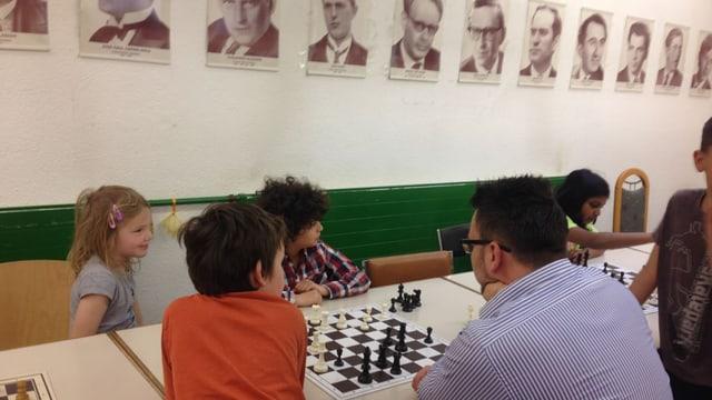 Schachtrainer Milos Milovanovic mit seinen jungen Schülern. An der Wand die Bilder alter, grosser Schachmeister.