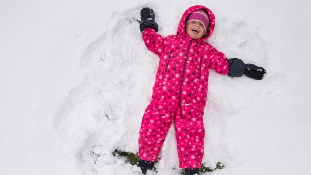 Ein Kind tollt im Schnee.