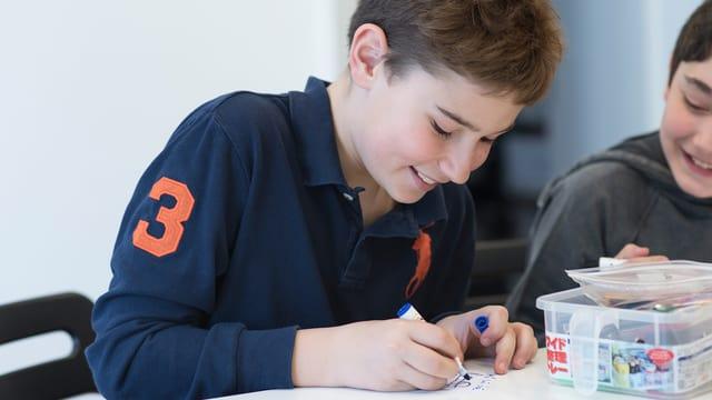 Ein Junge sitzt lachend an einem Tisch und zeichnet mit einem Buntstift auf einen Zettel.