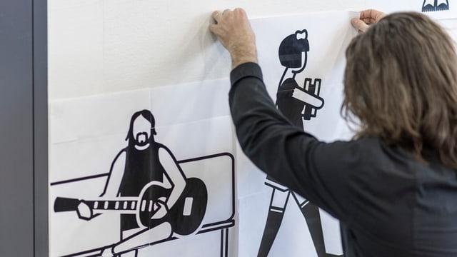 Schule für Gestaltung: Schüler hängt Zeichnung an die Wand.