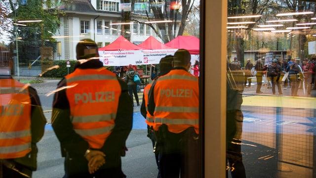 Die Polizei beobachtet eine politische Kundgebung.
