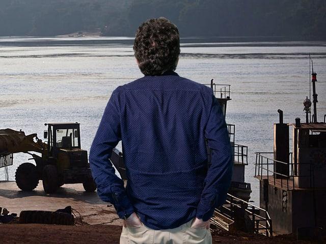 Thomas Häusler steht vor einem Bild von Arbeiten am Belo-Monte-Staudamm.