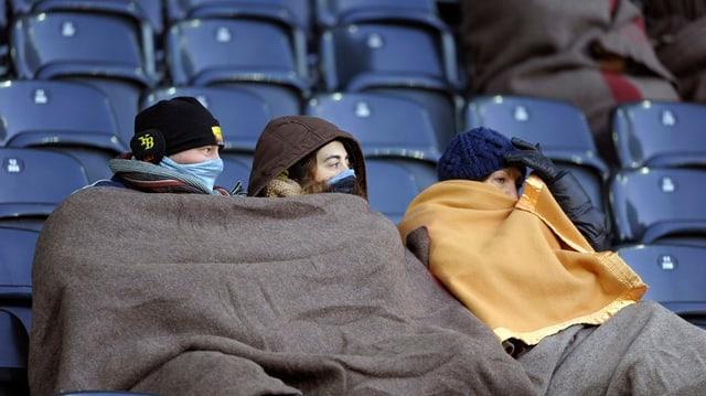 Fans im Stadion schützen sich mit Decken gegen die Kälte.