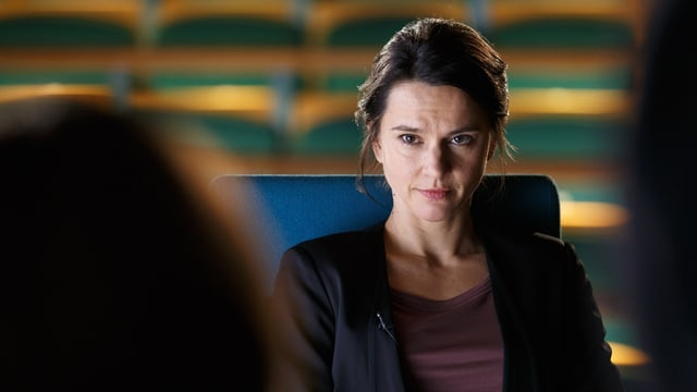 Kommissarin sitzt auf einem Stuhl und blickt in die Kamera, ihr gegenüber sitzt eine Person, von welcher man nur einen Teil des Hinterkopfs sehen kann.n