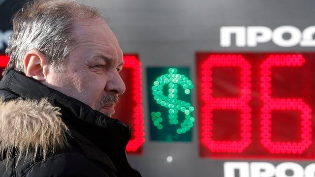 Ein Mann steht vor einer Leuchttafel mit dem aktuellen Rubel-Dollar-Wechselkurs.