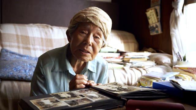 Eine late japanische Frau blättert in einem Fotoalbum.