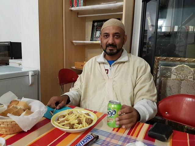 Der Journalist Shams Ul-Haq beim Essen im Speisesaal der Moschee.