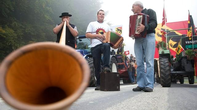 Ein Alphornbläser und zwei Handorgel-Spieler vor Berner Flaggen.
