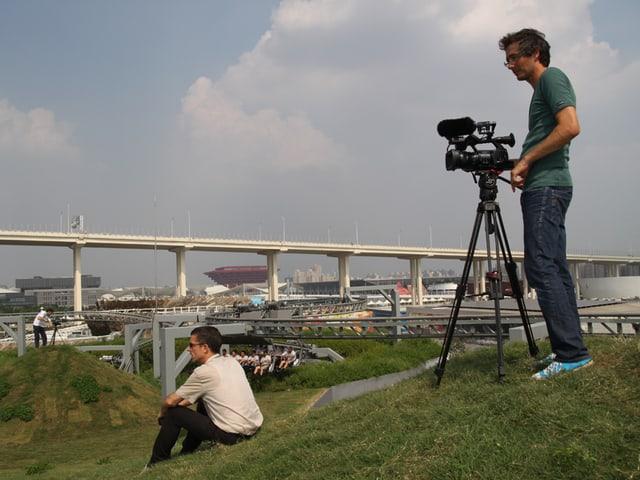 Ein Mann mit Kamera steht auf einem Grashügel. im Hintergrund die Stadt Shanghai.