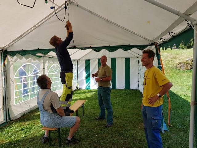 4 umens monteschan chazzolas en la tenda da la festa dil vitg