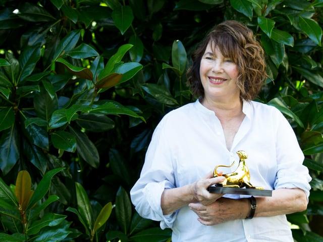 Jane Birkin hält eine goldene Leopardenstatue.
