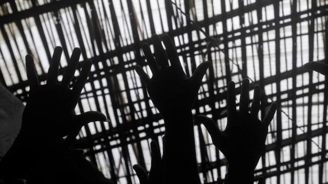 Ausgestreckte Hände vor einem Gefängnisgitter.