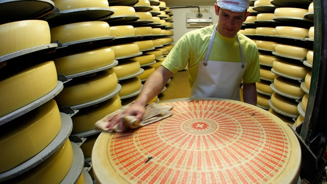 Ein Käser bearbeitet einen Laib Käse in einem Käselager.