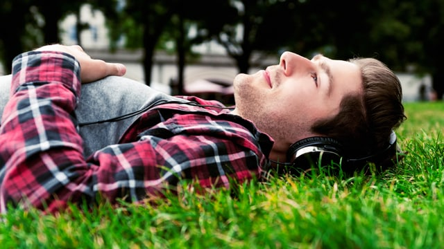 Mann liegt im Gras und trägt Kopfhörer