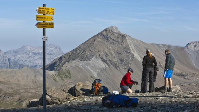 Wanderer stehen vor eine Wanderweg-Wegweiser in der Bergwelt.