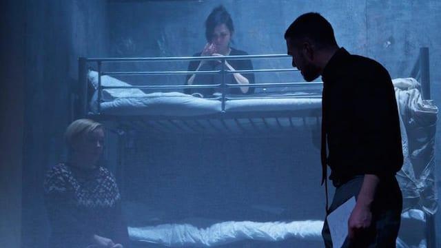Auf einer Theaterbühne steht ein Mann in aggressiver Haltung und schaut zwei Frauen an.