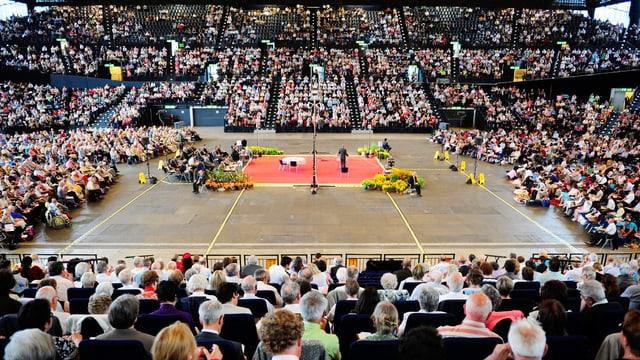 In einer riesigen Halle sitzen tausende Menschen in Reihen.