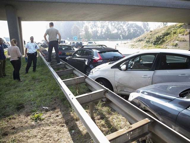 Leute stehen am Rande der Autobahn vor demolierten Autos