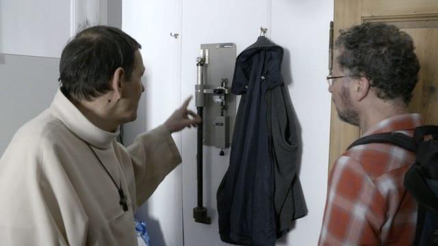 Zwei Männer schauen auf ein technisches Gerät, das an der Wand hängt.
