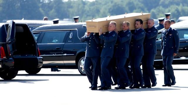 Männer tragen einen Sarg zum Leichenwagen.