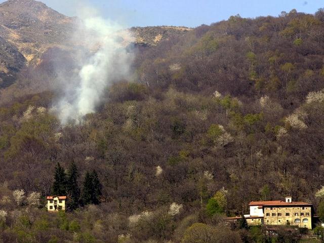 An einem Hang im Tessin steigen Rauchschwaden aus dem trockenen Bewuchs, die Aufnahme stammt von Ostern 2001.