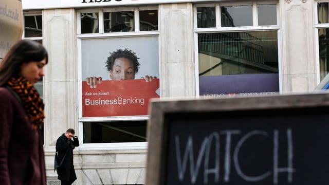 Ein Werbeplakat der HSBC-Bank. Davor laufen Leute vorbei.