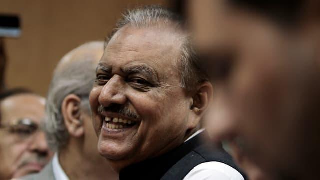 Mamnoon Hussain schaut mit einem Lächeln an der Kamera vorbei.