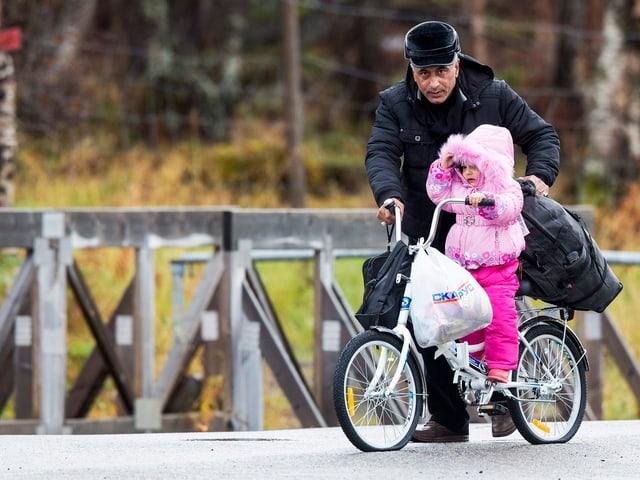 Ein Mann mit einem Kind auf einem Fahrrad überquert eine Brücke.