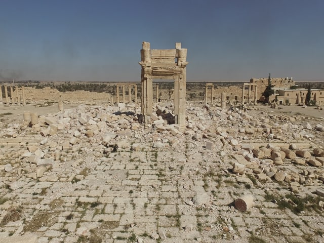 Ein antiker Steinbogen steht alleine inmitten von Trümmern.