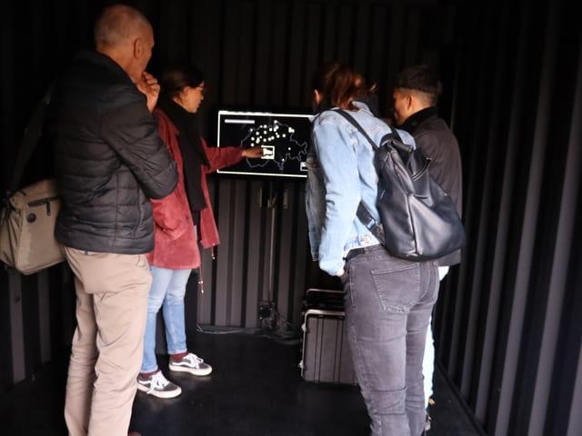Besucher vor einem Bildschirm