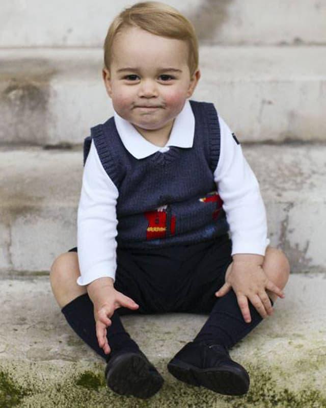 Prinz George in blauem Gilet auf einer Steintreppe sitzend.