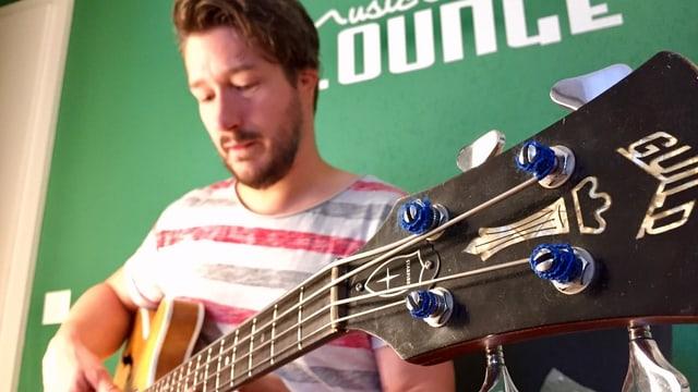 Ein junger Mann spielt Bassgitarre