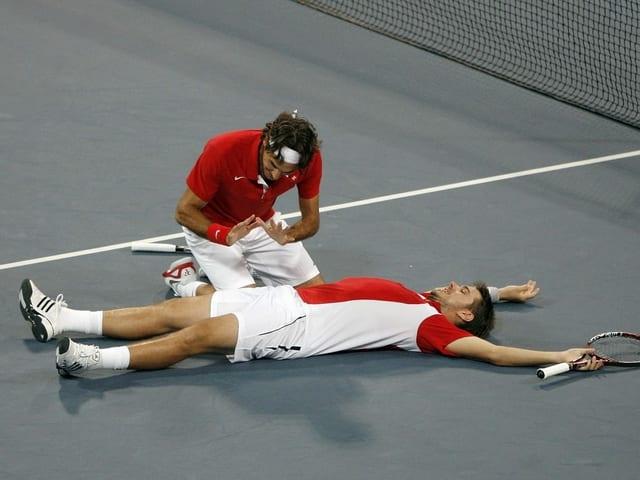 Roger Federer wärmt sich symbolhaft seine Hände am brennenden Stan Wawrinka.