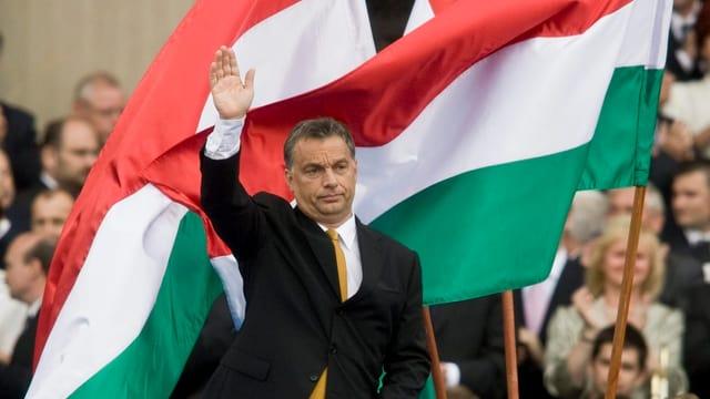 Orban steht vor Fahnen und winkt