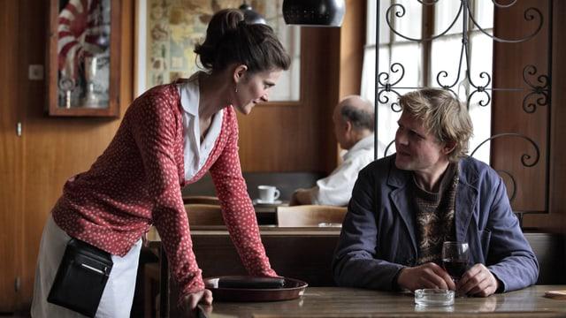 Filmszene: Ernst sitzt in einer Beiz am Tisch, die Kellnerin Regula stützt sich auf den Tisch und spricht mit Ernst.