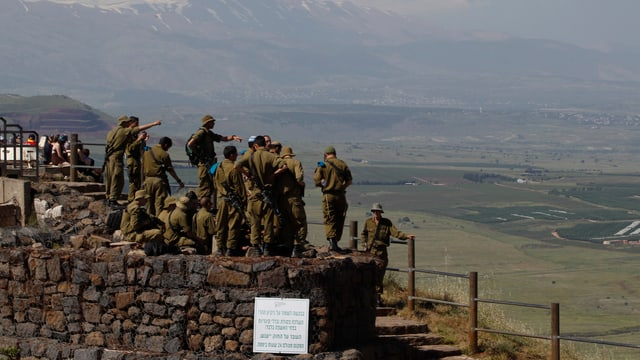 Israelische Soldaten stehen auf einem Hügel und werden gebrieft.