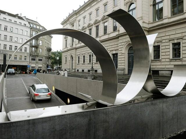 Blick durch die Skulptur aus Chromstahl auf die Parkhausrampe