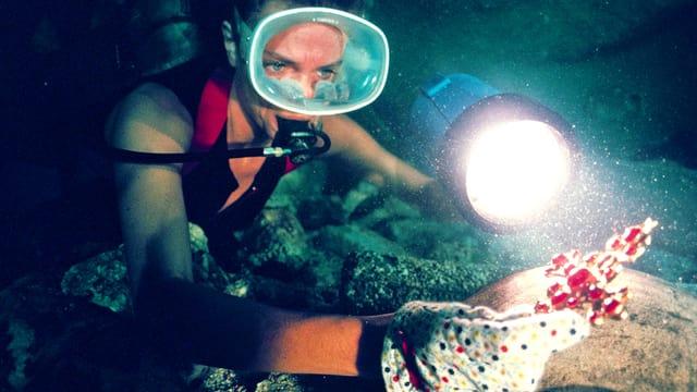 Eine Taucherin hält ein Schmuckstück in der Hand, das sie mit einer Lampe beleuchtet.