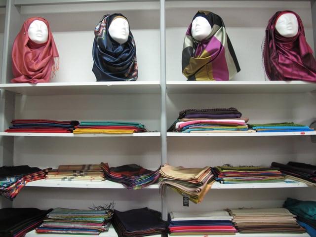 Ein Wandregal voll mit Kopftüchern - sogenannten Hijabs - in allen Farben und Mustern.