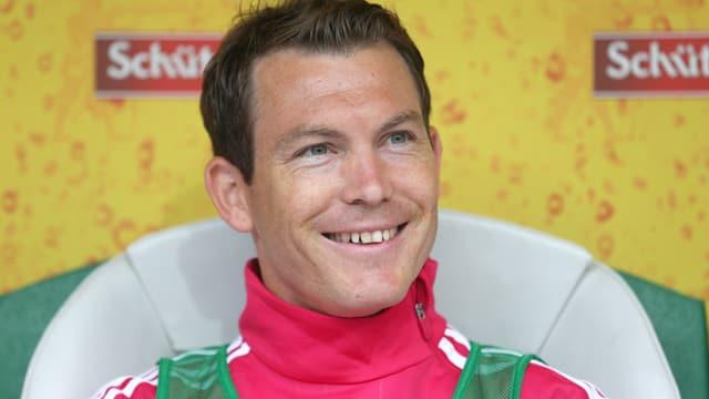 Stephan Lichtsteiner sitzt lächelnd auf der Ersatzbank.