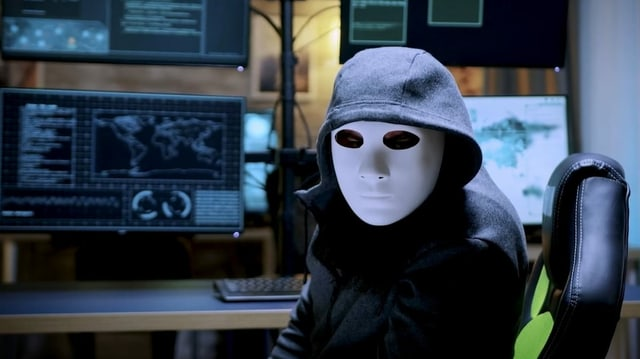 Ina persuna cun capuza e mascra alva davant in computer.