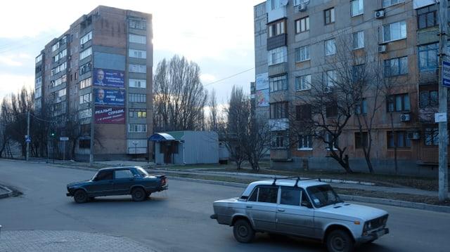 Strasse mit zwei Autos. im Hintergrund Wohnblöcke.