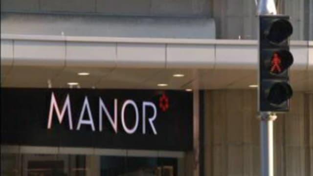 Manor-Schriftzug mit roter Ampel