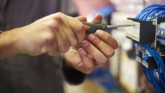 Symbolbild: Ein Mann schraubt an einer elektrischen Installation.