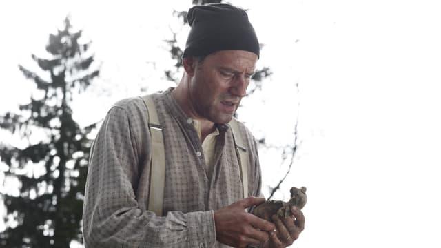 Ein Mann mit Hemd, Hosenträgern und Zipfelmütze schaut auf eine verfaulte Kartoffel in seiner Hand. Im Hintergrund sieht man ein paar Tannen.