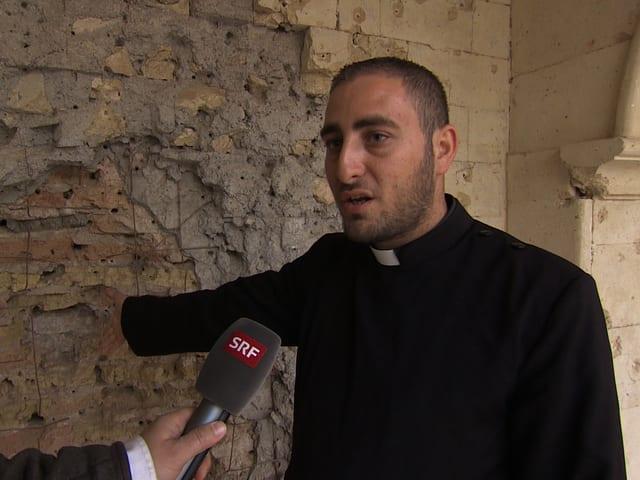 Priester zeigt Einschusslöcher.