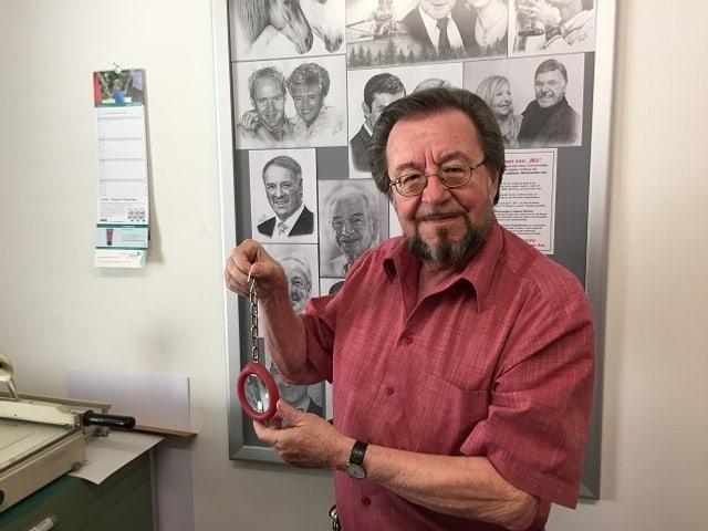 Der Erfinder präsentiert in seinem Atelier eine Lupe mit einer Kette.