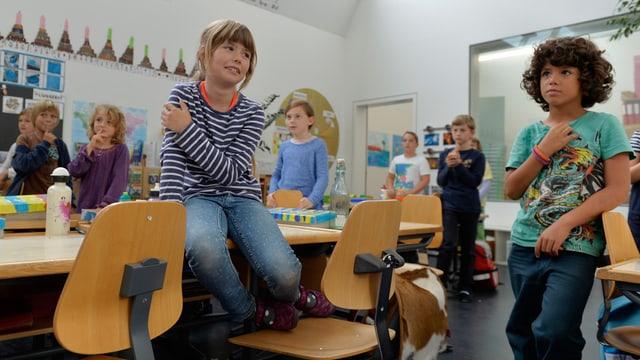 Ein Schulzimmer mit Tischen und kleinen Kindern.