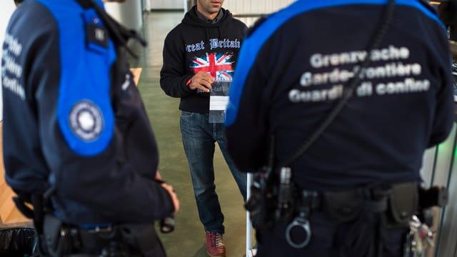 Zwei Grenzwächter in Uniform von hinten fotografiert stehen vor einem Mann, der einen Pullover mit der Flagge des Vereinigten Königreichs trägt.